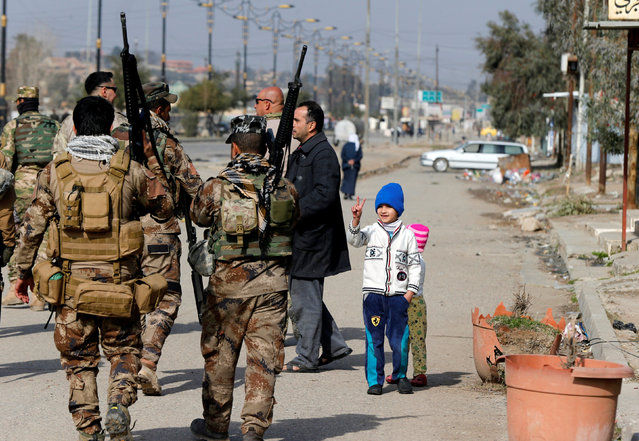Members of the Iraqi army carry weapons during an operation to search for weapons in the Arabi neighborhood in Mosul, Iraq January 26, 2017. (Photo by Muhammad Hamed/Reuters)