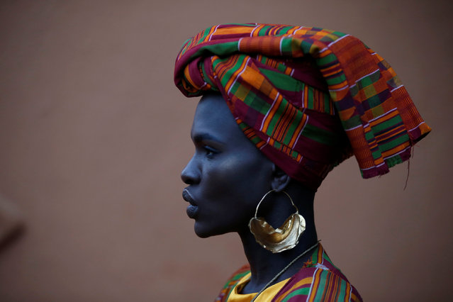 "A Kenyan model Ajuma Nasanyana waits behind the scenes before the fashion show showcasing African fashion and culture during a gala marking the launch of a book called ""African Twilight: The Vanishing Rituals and Ceremonies of the African Continent"" at the African Heritage House in Nairobi, Kenya on March 3, 2019. (Photo by Baz Ratner/Reuters)"