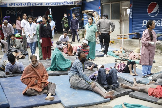 Health workers take care of injured people outside the Manmohan Memorial Community Hospital after an earthquake caused serious damage in Kathmandu, Nepal, 25 April 2015. (Photo by Narendra Shrestha/EPA)