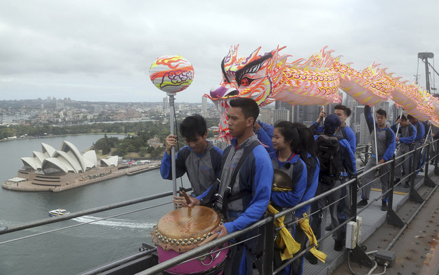 A troupe of Chinese Dragon dance performers make their way to a top of the Sydney Harbor bridge with The Sydney Opera House in the background, in Sydney, Australia, Tuesday, January 21, 2014. A troupe of dragon dancers and musicians made their way to the top of the Sydney icon ahead of Chinese New Year celebrations which falls on Friday, January 31. (Photo by Rob Griffith/AP Photo)