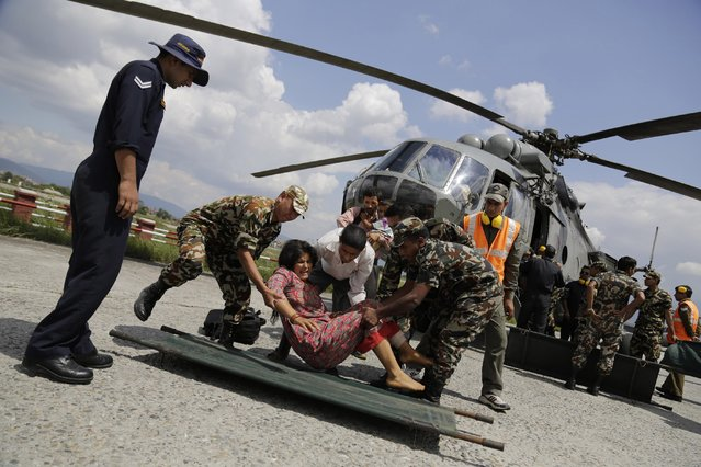 A woman injured in Saturday's earthquake, is laid on a stretcher after being evacuated in an Indian Air Force helicopter at the airport in Kathmandu, Nepal, Monday, April 27, 2015. The death toll from Nepal's earthquake is expected to rise depended largely on the condition of vulnerable mountain villages that rescue workers were still struggling to reach two days after the disaster. (Photo by Altaf Qadri/AP Photo)