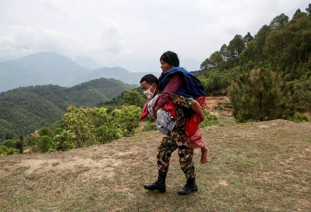A Nepal Army personnel carries an injured woman to a helicopter following Saturday's earthquake in Sindhupalchowk, Nepal, April 28, 2015. (Photo by Danish Siddiqui/Reuters)