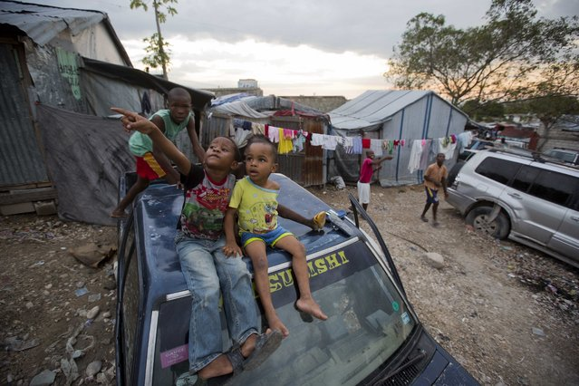 In this December 5, 2016 photo, children sit on a parked car in the Delmas tent camp set up nearly seven years ago for people displaced by the 2010 earthquake, in Port-au-Prince, Haiti. The number of people in these makeshift communities has declined since the immediate aftermath, but those who remain are a stubborn reminder that this impoverished country has yet to fully recover from one of the worst natural disasters in history. (Photo by Dieu Nalio Chery/AP Photo)