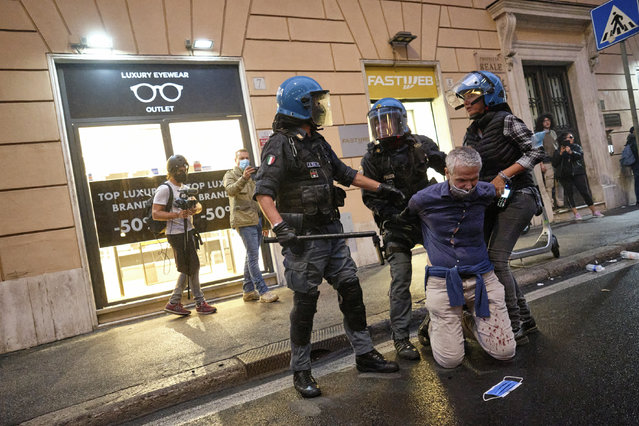 A demonstrator is apprehended by police officers after clashes during a protest, in Rome, Saturday, October 9, 2021. (Photo by Mauro Scrobogna/LaPresse via AP Photo)