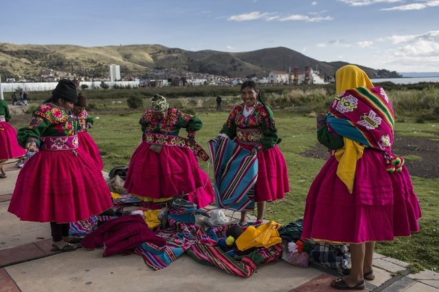 In this January 29, 2017 photo, dancers put on their costumes near the shore of Lake Titicaca prior to their performance for Virgin of Candelaria celebrations in Puno, Peru. Some competing groups wear shoes made with alpaca skin, collars hung with ears of corn and hats adorned with old coins or the bright-colored feathers of Amazonian birds. (Photo by Rodrigo Abd/AP Photo)