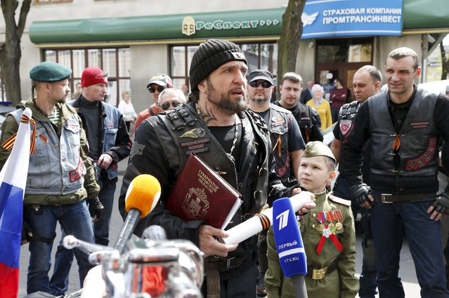 "Leader of the motorcycling club Night Wolves, Alexander Zaldostanov (C, front), nicknamed ""Khirurg"" (Surgeon), addresses the media in Brest, Belarus, April 28, 2015. Russia on Monday demanded an explanation from Poland as to why it denied entry to a group of Russian bikers commemorating the 70th anniversary of the end of World War Two. (Photo by Vasily Fedosenko/Reuters)"