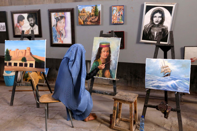 An Afghan woman paints during a painting session in Herat, Afghanistan, April 27, 2015. The Afghan government and international community have turned their back on female human rights defenders threatened by mounting violence, Amnesty International said 07 April. It said professionals and activists were not only targeted by the Taliban militants but also by warlords and government officials, and face threats, sexual assault and assassinations. (Photo by Jalil Rezayee/EPA)