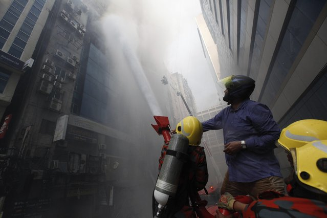 A commuter watches firefighters work to douse a fire in a multi-storied office building in Dhaka, Bangladesh, Thursday, March 28, 2019. A fire in a high-rise office building in Bangladesh's capital on Thursday killed seven people and injured dozens more, police said. (Photo by Mahmud Hossain Opu/AP Photo)