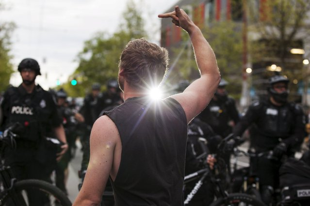 A demonstrator swears at police while holding a middle finger up during an anti-capitalist protest in Seattle, Washington May 1, 2015. (Photo by David Ryder/Reuters)