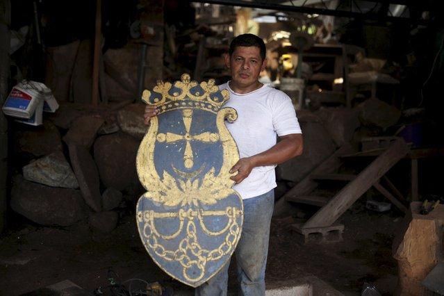 Jose Sabas Gomez displays a shield salvaged from a demolished church in his workshop in Apastepeque, El Salvador March 9, 2016. (Photo by Jose Cabezas/Reuters)