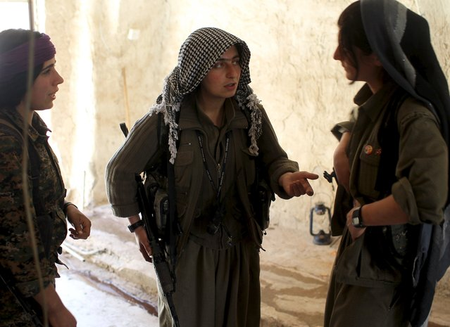 Female Kurdistan Workers Party (PKK) fighters discuss tactics to reach a position which had been hit by Islamic State car bombs in Sinjar, March 11, 2015. (Photo by Asmaa Waguih/Reuters)