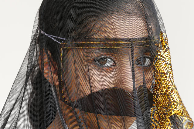An Emirati girl wears a traditional outfit, worn in her village by elderly women, during the al-Gharbia Watersports festival poses near al-Mirfa beach, outside Abu Dhabi, on May 2, 2015. (Photo by Karim Sahib/AFP Photo)
