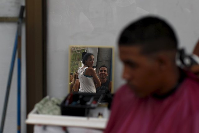 Cuban migrants are reflected in a mirror as another gets his hair cut at an old hotel used as a provisional shelter in Paso Canoas, at the border with Costa Rica, in Panama March 21, 2016. (Photo by Carlos Jasso/Reuters)