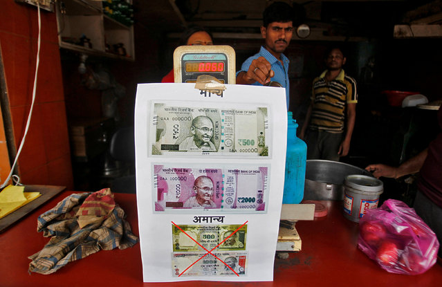 A notice is pasted at a shop stating the refusal of the acceptance of the old 500 and 1000 Indian rupee banknotes and acceptance of the new 500 and 2000 Indian rupee banknotes, in Allahabad, India, November 10, 2016. (Photo by Jitendra Prakash/Reuters)