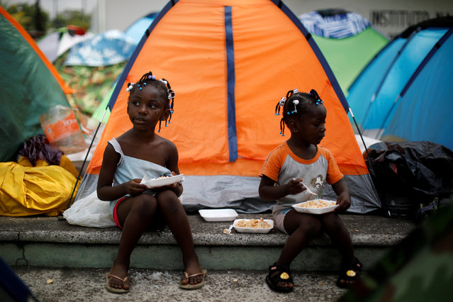 Girls from Congo eat outside their tent at an improvised camp outside the premises of the National Migration Institute (INM), in Tapachula, Mexico April 7, 2019. (Photo by Jose Cabezas/Reuters)