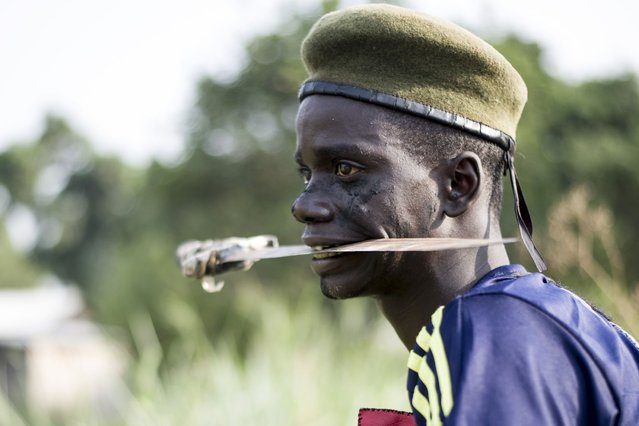 """A member of the mainly Christian """"anti-balaka"""" (anti-machete) militia holds a blade in his mouth as he trains in the Boeing neighbourhood of Bangui, Central African Republic, on February 24, 2014. Two Chadian soldiers, three Muslim civilians and two Christian militiamen were killed in another weekend of violence in Bangui but France's top commander on February 24 denied claims of ethnic cleansing. Paris sent troops to the Central African Republic in December 2013 amid talk of an impending genocide as sectarian unrest escalated in the aftermath of a coup. (Photo by Fred Dufour/AFP Photo)"""
