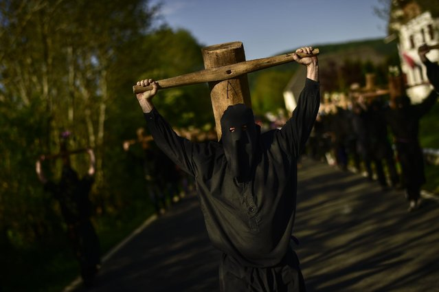 """Masked penitents holds their crosses  during spring """"Romeria Cruceros de Arce"""", while they walk alongside Villanueva de Arce and Roncesvalles northern Spain Sunday, May 10, 2015. Every year on the second Sunday in spring, people with crosses march from their small Pyrenees towns to Roncesvalles Church in tribute of the Virgin. (Photo by Alvaro Barrientos/AP Photo)"""