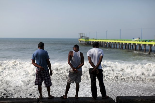 Fishermen watch the waves in La Libertad May 13, 2015. (Photo by Jose Cabezas/Reuters)