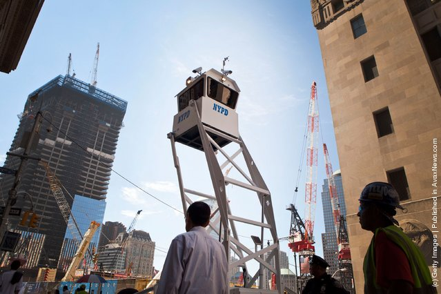 People walk underneath a New York Police Department mobile observation tower outside of Ground Zero