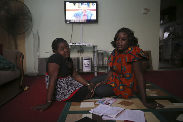 Adetola Ibitoye, 39, sits with her daughter Iteoluwa Ibitoye, 9, in their home in Omole district, Lagos February 16, 2014. When Adetola was growing up, she wanted to run a fashion business. Now she is a clothes designer. Adetola says she wants her daughter to be the best at whatever she sets her mind to be. Her daughter Iteoluwa says she wants to grow up to be a university teacher. (Photo by Akintunde Akinleye/Reuters)