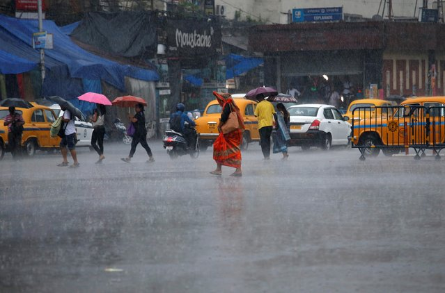 Commuters cross a road during heavy rains in Kolkata, India, May 3, 2019. (Photo by Rupak De Chowdhuri/Reuters)