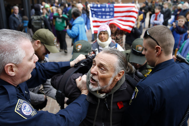 Police detain a protester demonstrating in opposition to the proposed Keystone XL oil pipeline, Monday, March 10, 2014, outside the Federal Building in Philadelphia. The protestors say the pipeline would contribute to global warming. (Photo by Matt Rourke/AP Photo)
