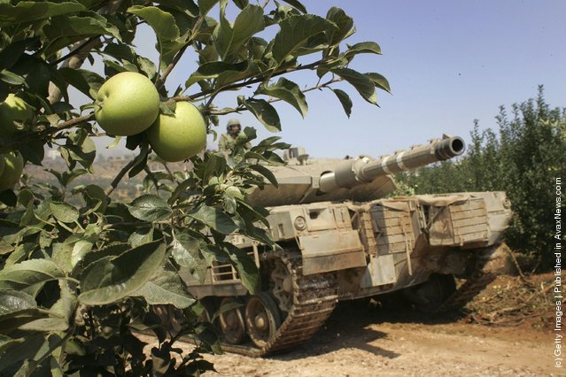 An Israeli tank moves through an apple orchard before entering Lebanon from the Israel Lebanese border