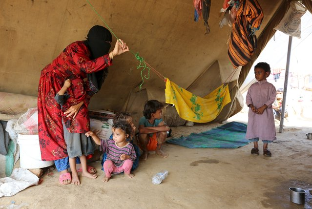 A woman and children are pictured in their tent at the Shawqaba camp for internally displaced people who were forced to leave their villages by the war in Yemen's northwestern province of Hajjah March 12, 2016. (Photo by Abduljabbar Zeyad/Reuters)