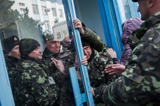Pro-Russian self-defense force members get through an entrance to the Ukrainian Navy headquarters in Sevastopol, Crimea, Wednesday, March 19, 2014. An Associated Press photographer said several hundred militiamen took down the gate and made their way onto the base. They then raised the Russian flag in the square by the headquarters. The unarmed militia waited for an hour on the square before the move to storm the headquarters. (Photo by Andrew Lubimov/AP Photo)