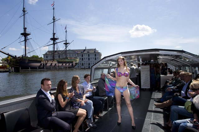 A model sports beachwear designed by Gottex during the Canal Catwalk fashion show with clothing dedicated to Kate, Duchess of Cambridge, during the first edition of the World Fashion Fair in Amsterdam, Netherlands, Thursday, May 21, 2015. At left is a replica of a 1749 Dutch East Indies Company merchant ship. (Photo by Peter Dejong/AP Photo)