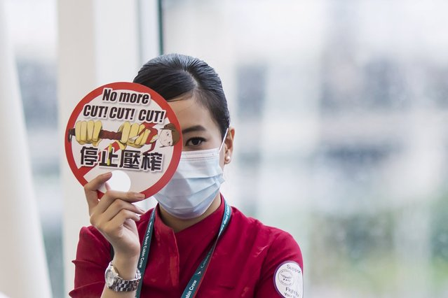 A Cathay Pacific flight attendant carries a sign while participating in a protest at the departure hall of the Hong Kong Airport, China May 19,2015. (Photo by Tyrone Siu/Reuters)