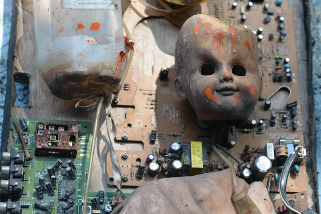 In this April 4, 2016 photo a cast-off baby doll fused with a motherboard of circuitry is displayed in an open-air museum and art workshop off a trash-strewn street cutting through some of the poorest neighborhoods in Port-au-Prince, Haiti. They were created by Haitian artists called Atis Rezistans who have become celebrated in the international art world by creating sculptures out of scrapped car parts, old wood, discarded toys and even human skulls found scattered outside crumbling mausoleums. (Photo by David McFadden/AP Photo)
