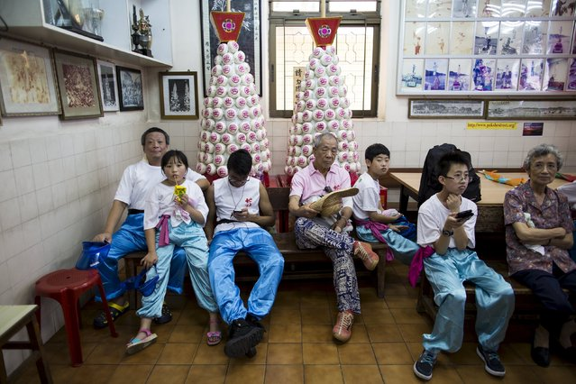 Participants rest in front of two small bun towers during a Bun Festival parade at Hong Kong's Cheung Chau island, China May 25, 2015. (Photo by Tyrone Siu/Reuters)