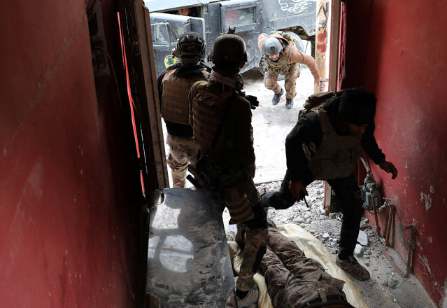 Iraqi special forces soldiers run inside a house during a battle with Islamic State militants in Mosul, Iraq March 3, 2017. (Photo by Goran Tomasevic/Reuters)