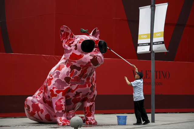 A worker wipes a dog sculpture outside a luxury fashion boutique under construction at the capital city's popular shopping mall in Beijing, Wednesday, June 5, 2019. Amid the trade war with the United States, Chinese President Xi Jinping is expressing confidence in the resilience of the Chinese economy. (Photo by Andy Wong/AP Photo)