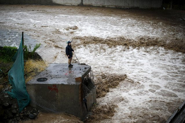 A man is seen next to a river during floods in Santiago, April 17, 2016. (Photo by Ivan Alvarado/Reuters)
