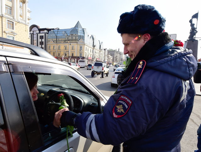A traffic policeman congratulates a female driver on upcoming International Women's Day in the citys Central Square in Vladivostok, Russia on March 7, 2017. (Photo by Yuri Smityuk/TASS via Getty Images)