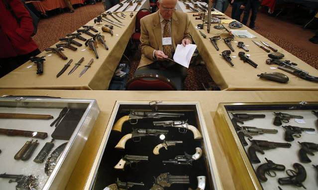 Antique gun collector Dave Kleiner reviews paperwork during the East Coast Fine Arms Show in Stamford, Connecticut, January 5, 2013. (Photo by Carlo Allegri/Reuters)
