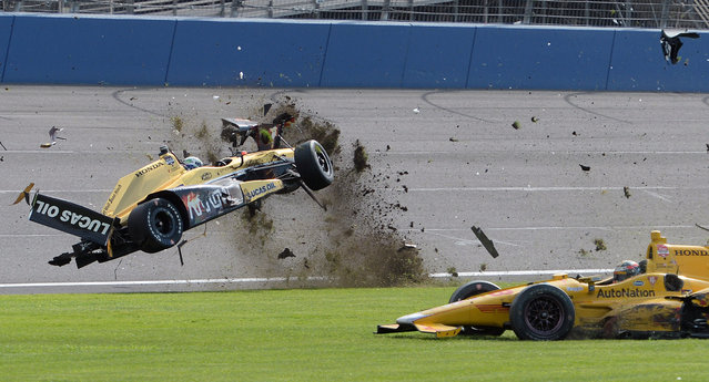 Ryan Briscoe, left, flips through the infield grass Saturday, June 27, 2015, during the IndyCar auto race at Auto Club Speedway in Fontana, Calif. (Photo by Will Lester/AP Photo)