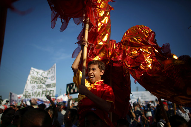 A boy reacts as he carries a Chinese dragon during a May Day rally in Havana, Cuba, May 1, 2016. (Photo by Alexandre Meneghini/Reuters)