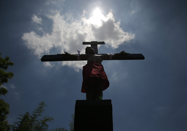 A Filipino devotee is nailed to a cross to re-enact the crucifixion of Jesus Christ in Santa Lucia village, Pampanga province, northern Philippines on Friday, April 18, 2014. Church leaders and health officials have spoken against the practice which mixes Roman Catholic devotion with folk belief, but the annual rites continue to draw participants and huge crowds. (Photo by Aaron Favila/AP Photo)