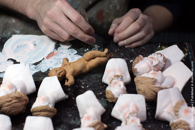 An artisan works on Neapolitan Christmas Nativity figurines at 'Maestri Ferrigno', which opened in 1836, at Via San Gregorio Armeno
