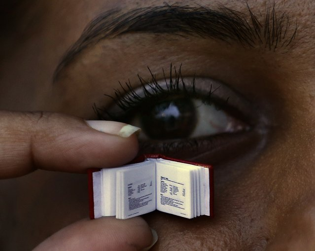 A woman holds up the small recipe book by Sri Lanka's iconic chef Publis Silva in Colombo April 24, 2014. The book is about 1cm by 1 cm (0.39 inch by 0.39 inch) and weight about 5 milligrams (0.00018 ounce), and there be 40 copies of it. (Photo by Dinuka Liyanawatte/Reuters)