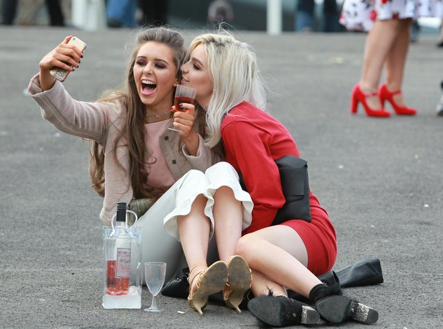 Two friends take a quick selfie during the Grand National Festival at Aintree Racecourse on April 6, 2017 in Liverpool, England. (Photo by WENN)