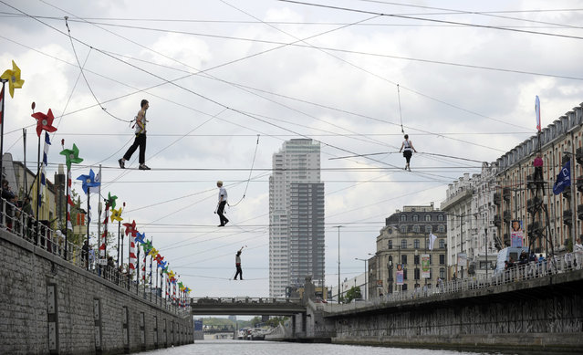 Tightrope walkers perform above a canal in Brussels April 26, 2014. Approximately forty-four tightrope walkers made an attempt to cross the canal during a performance. (Photo by Laurent Dubrule/Reuters)