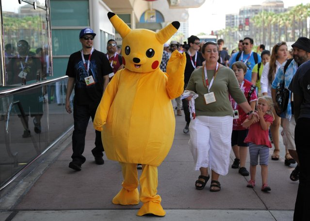 A fan dressed as Pokemon's Pikachu walks past the lines before Preview Night at Comic-Con International held at the San Diego Convention Center Wednesday July 8, 2015 in San Diego. (Photo by Denis Poroy/Invision/AP Photo)