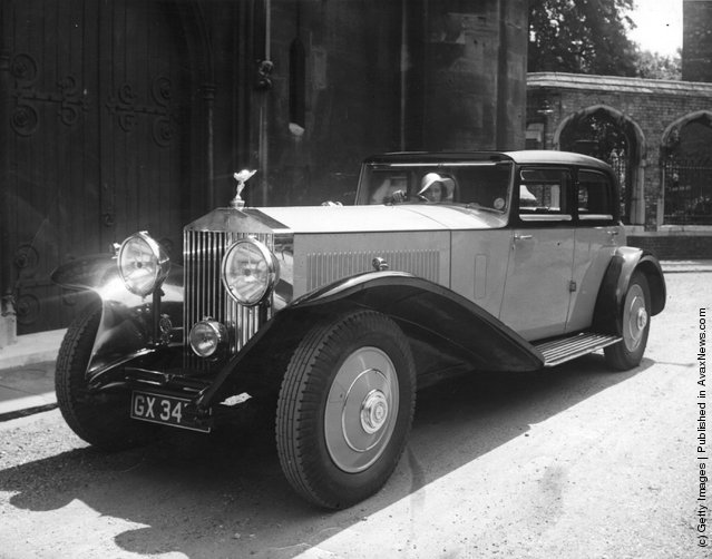 1935: A view of a vintage Rolls Royce limousine with a female driver