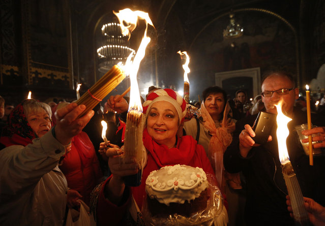 Ukrainian Orthodox faithful light candles from the Holy Fire brought from Jerusalem in St. Volodymyr Cathedral during the ceremony of the Holy Fire in Kiev, Ukraine, Saturday, April 15, 2017. The Holy Fire ceremony is part of Orthodox Easter rituals and the flame symbolizes the resurrection of Christ in a ceremony dating back to the 12th century. (Photo by Sergei Chuzavkov/AP Photo)