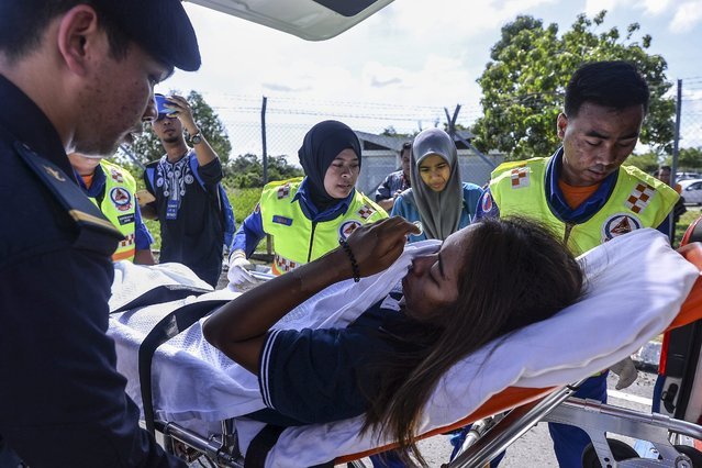 Tanjung Simpang Mengayau resort worker Armella Ali Hassan (C) is whisked away on a stretcher after arriving at Kota Kinabalu International Airport, Kota Kinabalu, Sabah state, Malaysia, 13 May 2016. Hassan and her three companions were reported missing on 02 May while on a two-hour boat ride from Pulau Balambangan to Simpang Mengayau in Sabah's northern Kudat district. All four were rescued by Malaysian authorities. (Photo by EPA/Stringer)