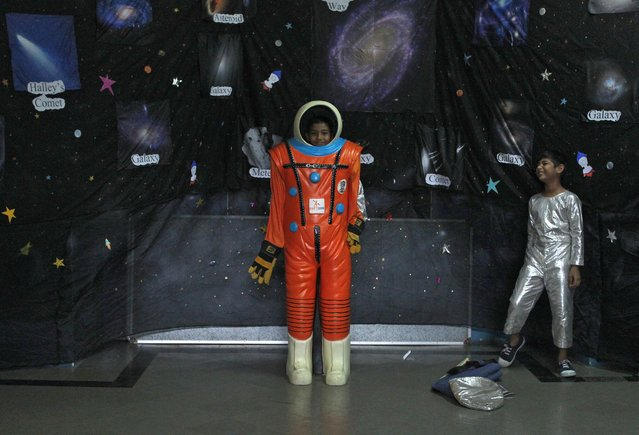 School children try on a space suit during an exhibition on space technology organised by Indian Space Research Organisation (ISRO) and a college in Mumbai, India, September 18, 2019. (Photo by Prashant Waydande/Reuters)